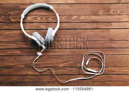 Headphones on brown wooden background