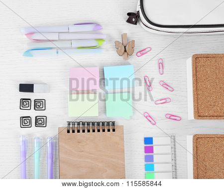 Notebook with stationery and pencil case on a white table