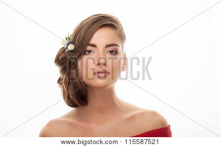 Closeup portrait of young adorable brunette woman with bun hairstyle and flower headpiece