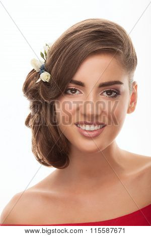 Closeup portrait of young smiling brunette woman with bun hairstyle and flower headpiece