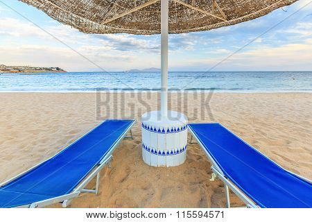 Umbrella and two empty deckchairs on the shore sand beach