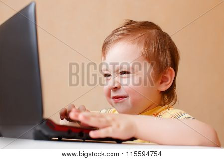 little smart boy surfing the Internet on laptop