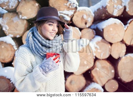 Beautiful young happy woman holding hot drink wearing knitted scarf and fedora hat covered with snow flakes. Pile of pine logs in the background. Snowing winter beauty and fashion concept.