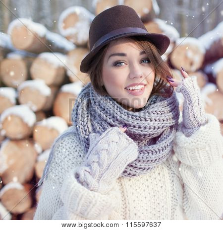 Beautiful young smiling woman, wearing knitted scarf and fedora hat covered with snow flakes. Pile of pine logs in the background. Snowing winter beauty and fashion concept.