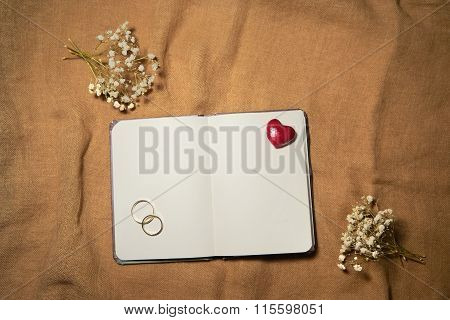 Blank Notebook With Heart And Wedding Rings On Sackcloth Background