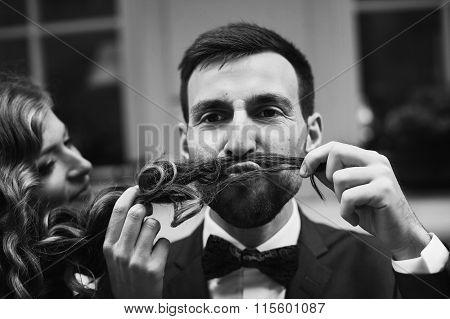 Beautiful Bride Having Fun And Making A Moustache With Her Hair For Handsome Groom Closeup B&w