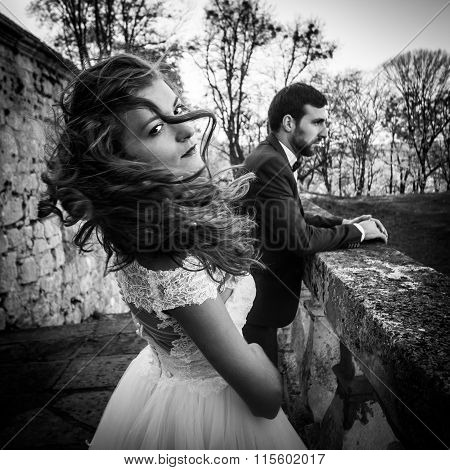 Beautiful Sexy Brunette Bride Waving Her Hair Near Her Husband And Old Castle Wall Closeup B&w