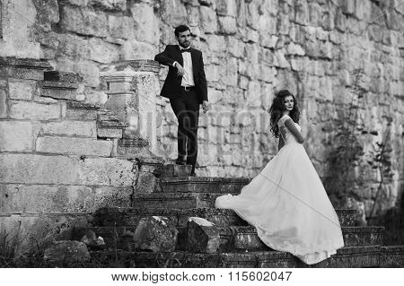 Romantic Valentyne Couple, Bride And Groom Posing At Destroyed Old Stairs Near Castle B&w