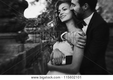 Handsome Sensual Groom Hugging Newlywed Bride From Behind At Old Castle Balcony B&w Closeup