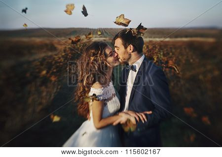 Fairytale Romantic Couple Of Newlyweds Hugging At Sunset In Vineyard Field Wth Leaves Flying