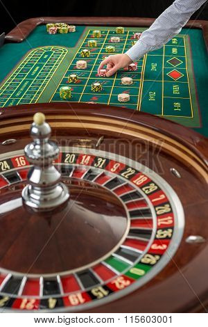 Roulette and piles of gambling chips on a green table.