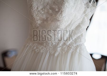Elegant Vintage White Dress On A Hanger In Luxury Hotel Room Closeup