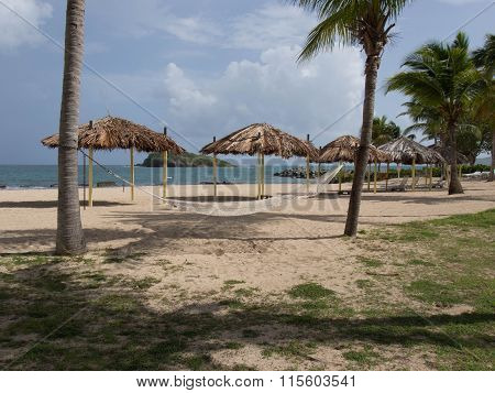 Hammock And Tiki Shelters On The Beach