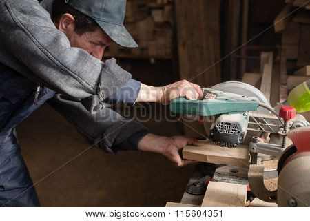 Carpenter sawing a board on a machine with a circulation saw in the carpentry workshop
