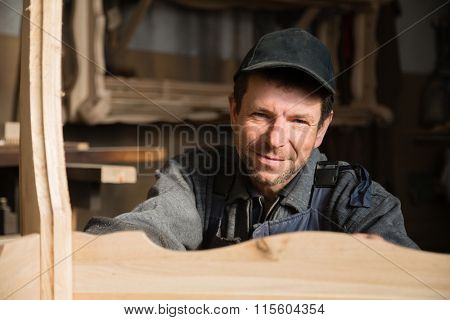 Portrait of a smiling carpenter in the carpentry workshop