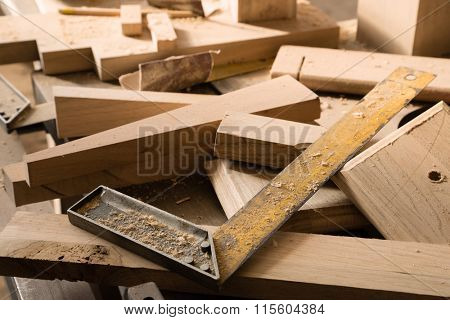 Billets of wood for furniture lie on a workbench in a carpentry workshop.