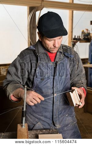 Carpenter works with wood in the carpentry workshop.