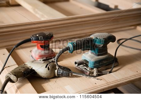 Carpentry tools - hand drill and a sander on a workbench in a carpentry workshop.