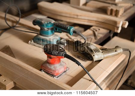 Carpentry tools- hand drill and a sander on a workbench.