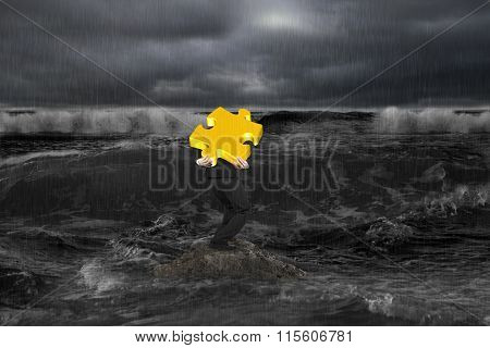 Businessman Carrying 3D Gold Puzzle On Rock In Dark Ocean