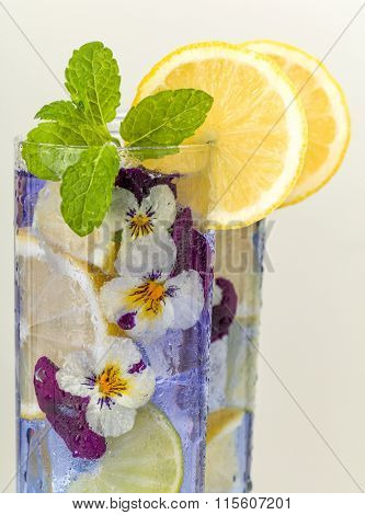 Cocktail drinks decorated with lemon and edible violet flowers
