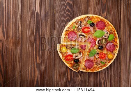 Italian pizza with pepperoni, tomatoes, olives and basil on wooden table. Top view with copy space