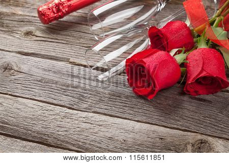 Red roses and champagne over wooden background. View with copy space