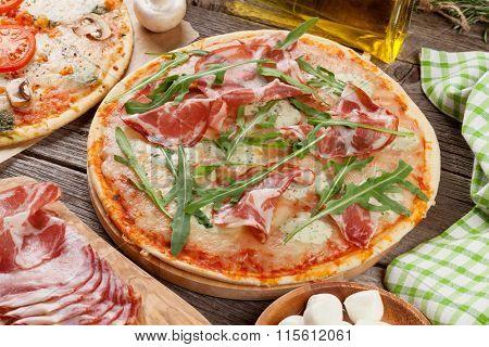 Pizza with prosciutto and mozzarella on wooden table
