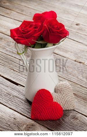 Red roses and hearts on wooden table. Valentines day concept