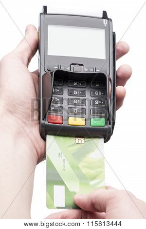 Man's hand holding a bank card on POS-terminal