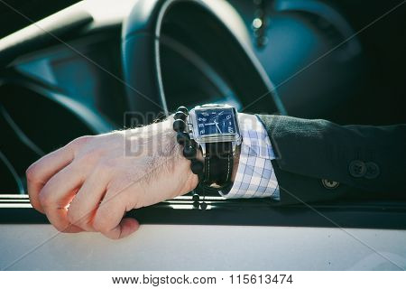 man hand in elegant suit with watch and bracelet lean on car window, closeup natural light, shallow depth of field