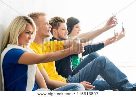 Group of happy students being on a break taking selfie. Focus on a happy boy. Background is blurry.