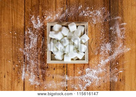 Aerial View of Sugar Cubes in Square Shaped Bowl with Unrefined Sugar spill over in Wooden Backgroun