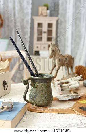 Objects and tools of creative hobby on a table in old-fashioned home.