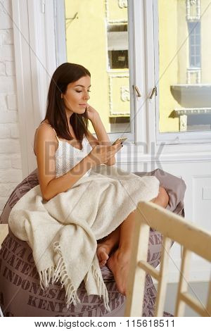 Young woman sitting at home, using mobilephone, texting.