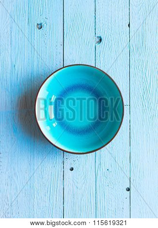 Colorful Blue EmptyDish over a light blue painted wood table with a simmetric position.