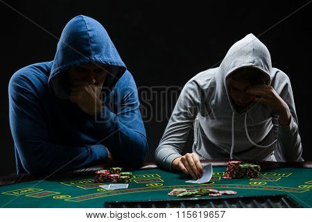 Two professional poker players sitting at a poker table
