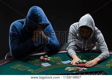Poker players sitting at poker table and going all-in
