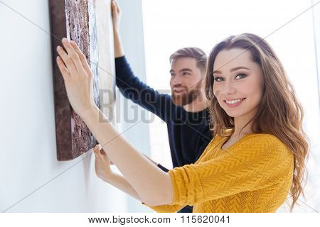 Cheerful couple hanging picture on the wall at home