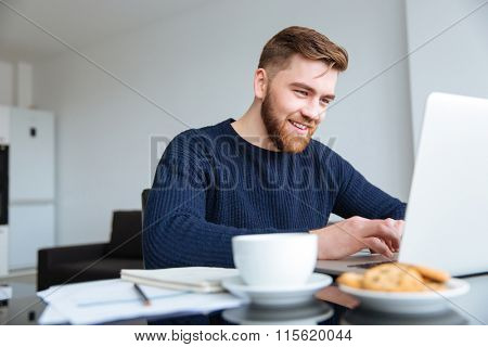 Portrait of a smiling man using laptop computer at home