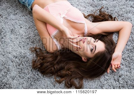 Seductive young female in pink bra lying on soft carpet and touching her face
