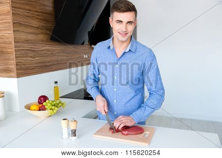 Happy handsome young male in blue shit standing and cutting meat on the kitchen