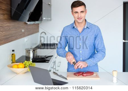 Attractive smiling young man in blue shit cooking meat on the kitchen at home