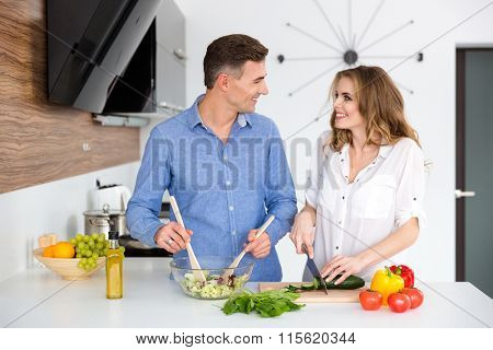 Portrait of a happy beautiful couple cooking together on the kitchen