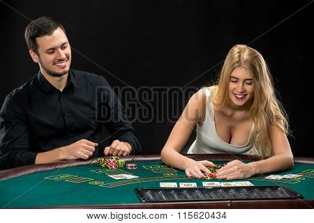Young couple playing poker, woman taking poker chips after winning