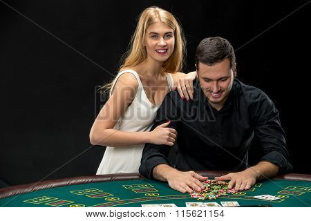 Young couple playing poker. Man taking poker chips after winning