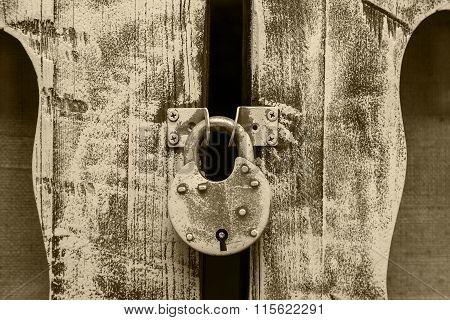 Closed Old Metal Lock Hanging On Wooden Door Hinges