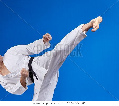 High kick athlete is beating with a black belt