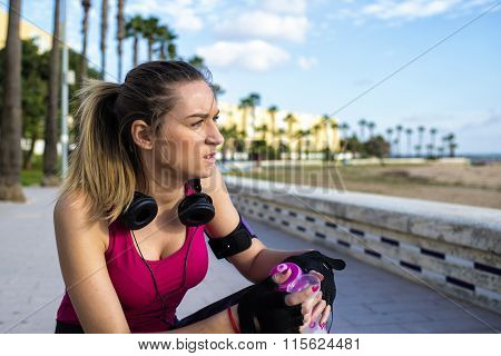 Young Blonde Sportswoman Relaxing After Running With Water Bottle