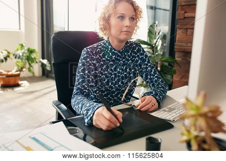 Female Graphic Designer Working At Her Desk